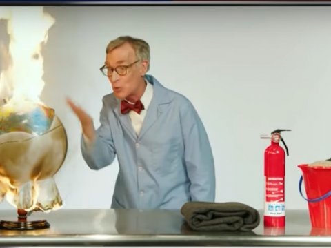 bill nye gestures at a globe that's on fire